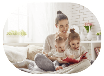 Seorang Ibu sedang Membacakan Buku Kepada Kedua Anaknya